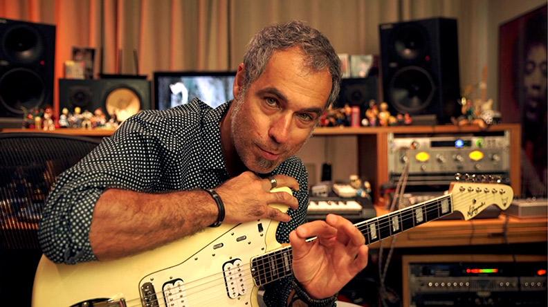 Homem sentando em um estúdio de gravação segurando uma guitarra no colo e fazer um Ok com a mão esquerda